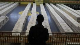 A soldier stands guard near boxes containing electoral papers for distribution at polling stations, at a gym in San Pedro Sula November 21, 2013