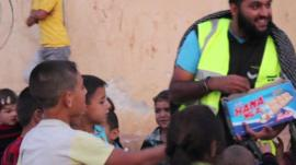 British man giving sweets to Syrian children