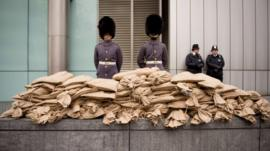 Soldiers stand guard over sacks of