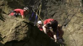 Rescue workers try to free the climber