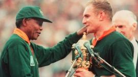 Francois Pienaar receives the Rugby World Cup from Nelson Mandela