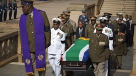 Military officers carry the coffin of former South African president Nelson Mandela into the Union Buildings in Pretoria for the three-day lying in state in Pretoria