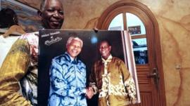 Pathe O with a picture of himself with Nelson Mandela