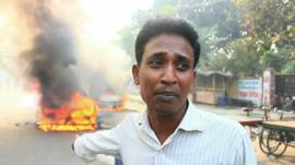 A man who's car has been torched during violent protests in Dhaka, Bangladesh