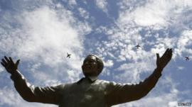 South African military jet fighters fly past a nine-metre (30ft) bronze statue of the late former South African President Nelson Mandela