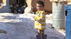 A Syrian child stands in the snow in a refugee camp in the Lebanese Bekaa valley