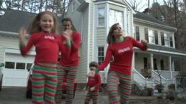 Family jumping around in Christmas pyjamas
