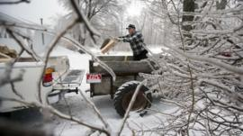 Ice from Monday's storm still clings to branches as Ken Finnegan loads his truck with firewood Thursday, Dec. 26, 2013, in Litchfield, Maine