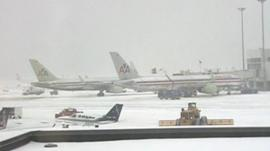 Snow plough on runway near passenger planes