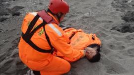 A Taiwanese Coast Guard treats Tseng Lien-fa after he was rescued from the sea