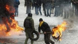 A man carries a burning tyre during clashes between police and protesters in Kiev