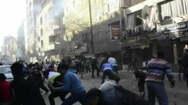 Men in street ducking as explosion rocks Cairo