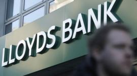 man walks past Lloyds Bank sign