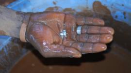 Ghanaian miner's hand holding mercury