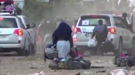 Woman carrying bags out of Homs