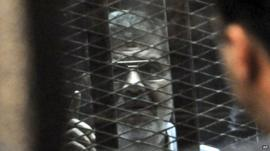 Mohammed Morsi speaks from a glassed-in defendant's cage during his trial over charges related to prison breaks
