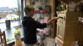 Boy posting letter into gold postbox