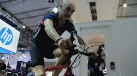 A cyclist demonstrates a new heart rate and blood sugar remote monitoring device at the Mobile World Congress in Barcelona