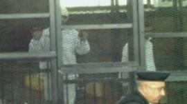 Defendants in court cage