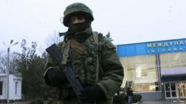 An armed man patrols at the airport in Simferopol, Crimea