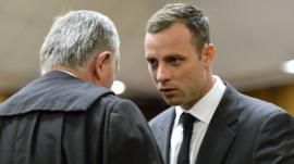 Oscar Pistorius, right, speaks with his lawyer Barry Roux as the start of his trial at the high court in Pretoria, South Africa