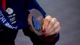 One of Scotland's curling team holding a Winter Olympics medal