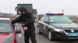 Border guard with car as OSCE vehicles pass