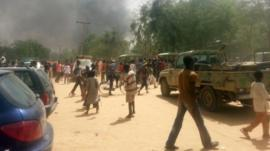People walk in a street as smoke rises after Boko Haram Islamists attacked a military base in the northeast Nigerian city of Maiduguri on March 14, 2014