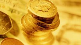 Pound coins stacked on banknotes