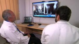 Doctors using a webcam to talk to a patient