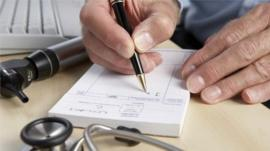 A GP writing a prescription (posed by a model)