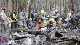 Personnel from the Washington National Guard join civilian workers in efforts to find the missing