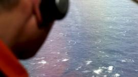 A crew member looks out of a window of a search plane