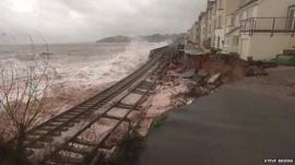 Waves crash over the suspended railway line in Dawlish