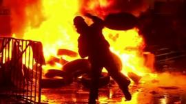 Protester throwing tyre onto fire
