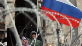 Pro-Russian activists wave a Russian flag and shout slogans
