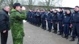 Man in military wear salutes police officers