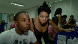 A man and woman use a computer at an internet access centre in Cuba
