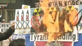Protesters set fire to banners with portraits of North Korean leaders