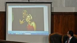 judge looks on as pictures are displayed during the trial of 20 indivuduals, including three Al-Jazeera journalists, in Cairo