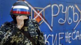 A pro-Russian militant adjusts his mask in Sloviansk , eastern Ukraine- slogan reads 'Russia do not surrender'