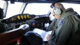 A pilot checks a map during the search for the missing Malaysian airliner