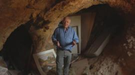The BBC's Jeremy Bowen inside a cave being used as a home on the West Bank