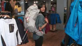 Sumi Das wears a backpack in a shop