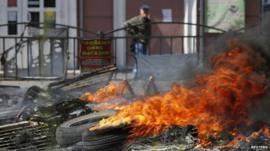 Man walks past burning barricade