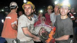Men help a rescued miner after Turkey blast