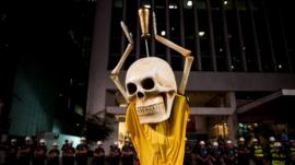Demonstrator wearing skull and Brazilian football strip