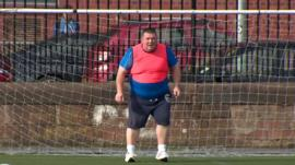 Man standing in football goal