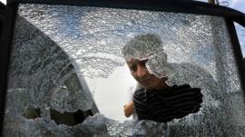 A local looks at a damaged vehicle following a gun battle