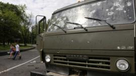 A couple walks past a wrecked Kamaz truck as they flee an area near the Donetsk airport